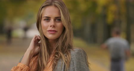 crows feet : Close-up portrait of beautiful Caucasian woman standing in autumn park and tucking hair. Pretty girl in checkered jacket and mustard dress turning to camera and smiling. Cinema 4k footage ProRes HQ.