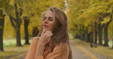 マスタード : Close-up portrait of cute Caucasian girl standing in autumn park and sighing. Attractive woman in mustard dress with tweed print holding long brown hair in wind. Cinema 4k footage ProRes HQ.