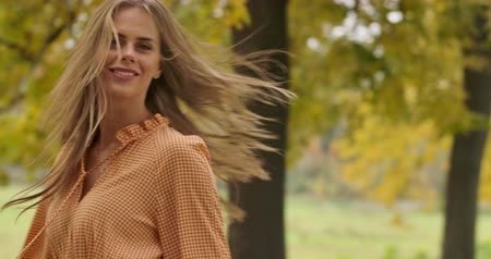 crows feet : Smiling Caucasian girl with long brown hair and green eyes spinning in the autumn park. Elegant woman in mustard dress with crows feet print having fun in the autumn park. Cinema 4k footage ProRes HQ
