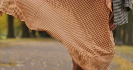 crows feet : Close-up of a mustard dress with tweed print blowed by the wind. Caucasian female legs showing up from under the dress. Cinema 4k footage ProRes HQ. Stock Footage