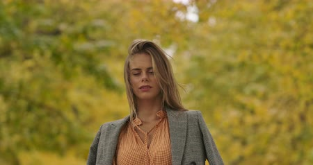 crows feet : Young Caucasian girl with green eyes standing on the background of autumn leaves and looking at camera. Woman in mustard dress and checkered jacket holds long hair in wind Cinema 4k footage ProRes HQ