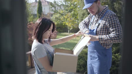 партия : Positive Caucasian male courier in blue work clothes giving box to the female customer and waiting for her to sign the waybill. Home delivery service, online shopping.
