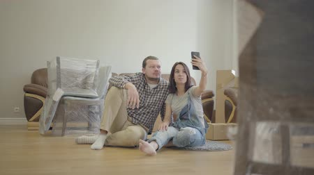 liga : Happy Caucasian couple sitting on the floor in living room with new furniture and making video call. Smiling couple moving in their new house. Start of new life.