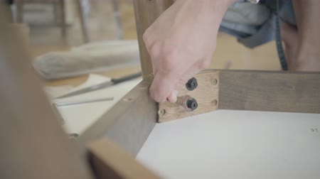 locksmith : Close-up of male Caucasian hands tightening screws with wrench. Adult locksmith working with wooden furniture.
