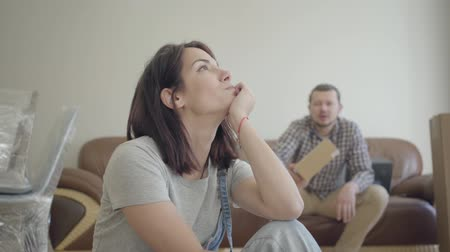 jealous : Irritated Caucasian woman sitting and looking away as her husband or boyfriend yelling on the background. Relationship problems in young family.