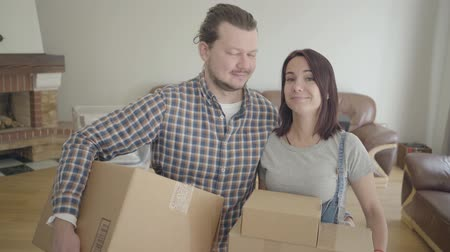 стенд : Portrait of Caucasian couple standing with cardboard boxes in living room and smiling. Happy young family moving in their new house. Soulmates starting living together.