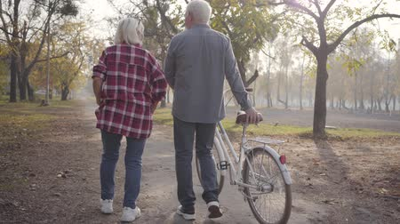 örök : Mature Caucasian couple walking with bicycle along the alley in the park. Happy retired senior family spending autumn evening outdoors. Aging together, eternal love concept.