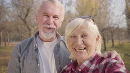 eternal : Close-up portrait of smiling Caucasian retired couple waving at camera. Mature European family standing in sunlight in the autumn forest. Aging together, eternal love concept Stock Footage