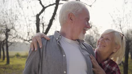 each other : Portrait of Caucasian mature family standing in sunlight in autumn forest and looking at each other. Happy senior European couple spending sunny evening outdoors. Aging together, eternal love concept Stock Footage