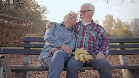 eternal : Portrait of a happy Caucasian retired couple sitting on the bench in sunlight and talking. Mature European family spending sunny evening outdoors. Aging together, eternal love concept.