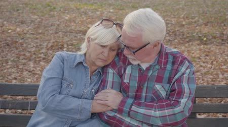 calming down : Portrait of a European retired couple sitting on the bench and talking. Mature husband calming down his beautiful senior wife. Aging together, eternal love concept.