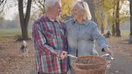 idoso : Happy senior Caucasian family standing in the autumn park with bicycle and talking. Smiling retired mature couple spending autumn evening outdoors. Aging together, eternal love concept.