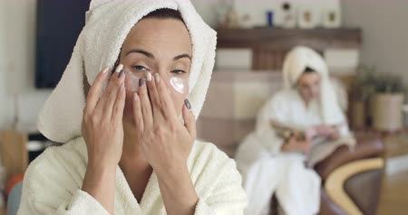 hidratáció : Pretty young Caucasian woman in white bathrobe and hair towel applying eye gel patches. Blurred girl in same clothes sitting on the background reading magazine. Cinema 4k footage ProRes HQ.