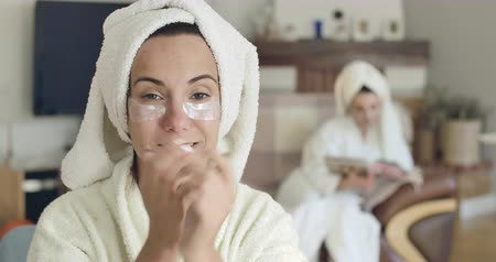 hidrasyon : Young cute Caucasian woman in white bathrobe and hair towel applying eye gel patches. Blurred girl in same clothes sitting on the background reading magazine. Cinema 4k footage ProRes HQ.