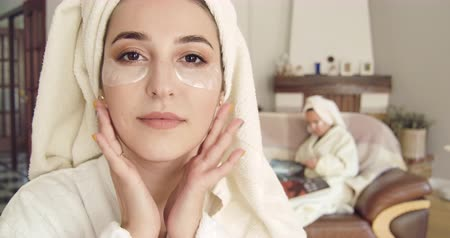 crema corporal : Closeup face of a young Caucasian woman in white bathrobe and hair towel applying eye gel patches. Blurred girl in same clothes sitting on the background reading magazine. Cinema 4k footage ProRes HQ