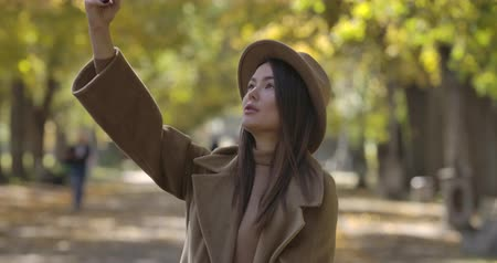 plezant : Young stylish Caucasian woman in brown hat taking selfie on smart phone in park. Beautiful European girl spending weekends outdoors. Cinema 4k footage ProRes HQ. Stockvideo