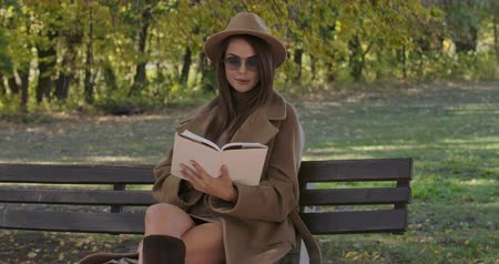 racconto : Intelligent Caucasian woman in sunglasses and brown hat sitting on bench and reading the book. Beautiful European girl enjoying free time in the autumn park. Cinema 4k footage ProRes HQ. Filmati Stock