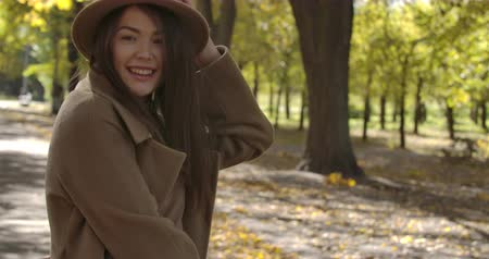 plezant : Smiling Caucasian girl in elegant hat spinning in the autumn park. Charming European woman with pleasant smile and brown hair having fun outdoors. Cinema 4k footage ProRes HQ. Stockvideo