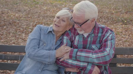 acalmar : Portrait of a Caucasian senior couple sitting on the bench and talking. Mature husband calming down his beautiful senior wife. Aging together, eternal love concept.