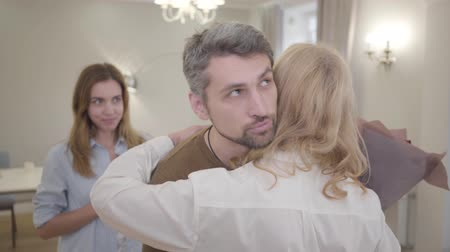 tahriş : Handsome Caucasian man giving bouquet of violet roses to blond woman and hugging her. Guy showing annoyed facial expression, and smiling together with his young beautiful wife. Insincerity, hypocrisy