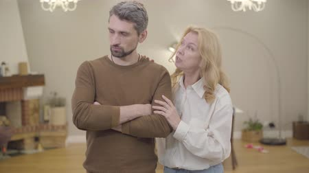 calming down : Senior blond Caucasian woman calming down bearded man with gray hair at home. Sad adult son sharing his problems with mother. Good family relationship, sympathy. Stock Footage