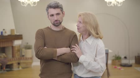 sosyal konular : Mature blond Caucasian woman distracting her sons attention from his problems at home. Adult bearded man with gray hair laughing with mother. Good family relationship, sympathy, support. Stok Video