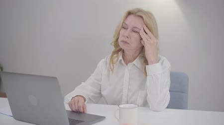distante : Portrait of sad thoughtful senior Caucasian woman sitting at the table with laptop. Mature business lady working at home. New technologies in modern life, home office, working online.