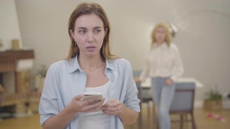 calming down : Portrait of young girl crying on the foreground. Mature blond Caucasian woman calming down her daughter at home. Sad adult lady sharing her problems with mother. Good family relationship, sympathy. Stock Footage
