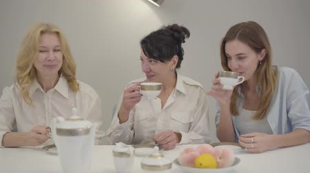 parentes : Three Caucasian women of different ages sitting at the table and drinking tea or coffee. Friends or family gathered together, talking and smiling. Happy people resting indoors.