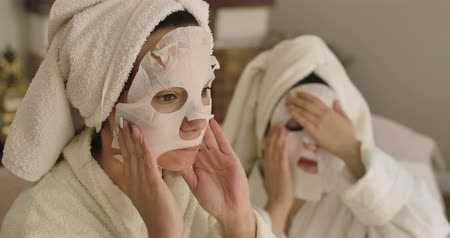 cuidados com a pele : Portrait of two adult Caucasian women applying face masks. Positive girls in hair towels and bathrobes resting at home. Cinema 4k footage ProRes HQ. Stock Footage