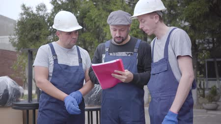 партия : Two adult Caucasian movers in helmets and blue uniform standing with their chief. Three workers reading waybill or consignment, planning work. Стоковые видеозаписи