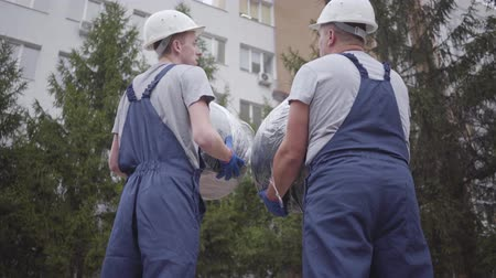 погрузчик : Back view of two Caucasian workers in white helmets and blue uniform holding packages. Men looking at each other, shaking heads and walking to the building.
