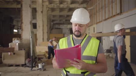 construtor : Close-up portrait of bearded Caucasian worker in white helmet walking at construction site, looking around and writing in documents. Other builders working at the background. Supervisor checking work. Vídeos