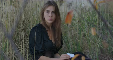 unlucky : Portrait of a beautiful Caucasian girl sitting in grass with a fragment of broken mirror and looking at the camera. Mysterious woman holding a symbol of bad luck in hands.