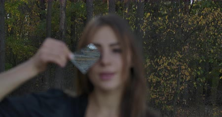 symbolismus : Young Caucasian girl holding fragment of broken mirror in front of her face. Autumn forest and lake reflecting in the crack. Mysterious woman with symbol of bad luck in hands.