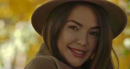 매력 : Close-up face of young charming European woman in brown hat posing at camera on the background of yellow leaves. Elegant Caucasian girl looking at camera and smiling. Cinema 4k footage ProRes HQ.