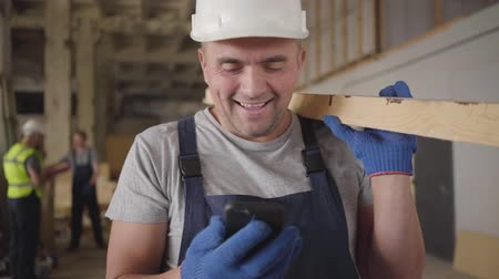 construtor : Portrait of adult Caucasian builder in white helmet laughing out loud as looking at smart phone. Strong muscular man standing at the construction site with wooden plank. Adult male builder at work.