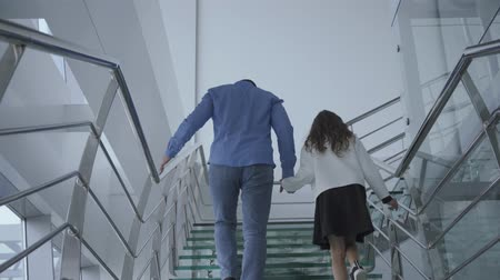 родственники : Back view of young father walking up the modern stairs in the airport with his daughter. Man and girl in casual clothes going to the departure or arrival area. Tourism, travelling, journey.