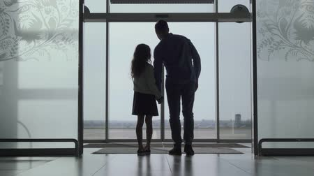 decolagem : Back view silhouette of little Caucasian girl showing her father airport runway. Young man and daughter waiting for the airplane takeoff. Travelling together, tourism, journey.