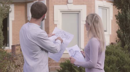 seçkin : Bearded Caucasian architect explaining project to his assistant in front of the house Young blond woman giving architectural drawings to the master. Professional teaching new employee secrets of work. Stok Video