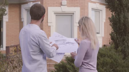 seçkin : Young handsome Caucasian man showing his client blueprints and the result of work. Professional architect standing with the satisfied customer in front of the newly built house. Stok Video