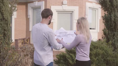seçkin : Male Caucasian architect and his female assistant examining blueprints in front of the house and giving high five. Professional contructor teaching new employee secrets of work.