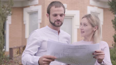 seçkin : Close-up of two Caucasian architects discussing blueprints outdoors. Professional female designer and her assistant examining drawings in front of the house. Professional occupation, creativity.