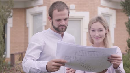 seçkin : Close-up of two Caucasian people standing in front of the house with blueprints and talking. Professional architects discussing architectutal drawings outdoors. Work, occupation, creativity.