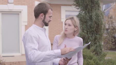 seçkin : Dissatisfied Caucasian female customer discussing the project with designer. Bearded architect explaining drawings to the client. Professional occupation, creativity, house design.