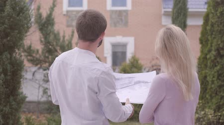 seçkin : Two young Caucasian people standing with architectural drawings and talking. Professional male and female architect discussing the idea. Constructors, house design, occupation. Stok Video