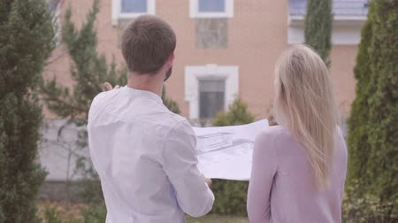 seçkin : Back view of young handsome Caucasian man showing his client blueprints and the result of work. Professional designer standing with satisfied customer in front of the house. People giving high five. Stok Video