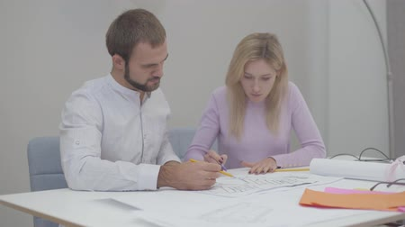 uygulanması : Professional Caucasian male designer teaching new employee in the office. Young pretty woman drawing blueprints. Specialists implementing ideas on paper.