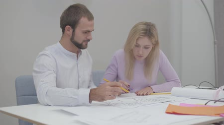 seçkin : Intelligent female Caucasian designer drawing blueprints at the office. Professional teaching male assistant to do drawings. Specialists implementing ideas on paper. Stok Video