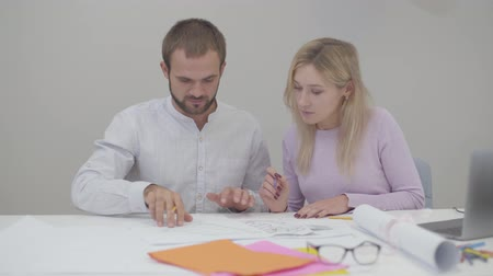 végrehajtás : Two professional Caucasian designers looking through blueprints in the office. Young pretty woman and handsome man implementing ideas on paper.